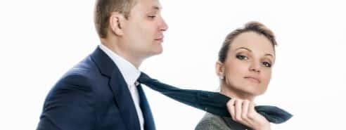 Женщина держит мужчину за галстук