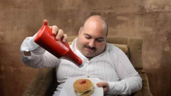 Мужчина кушает бургер